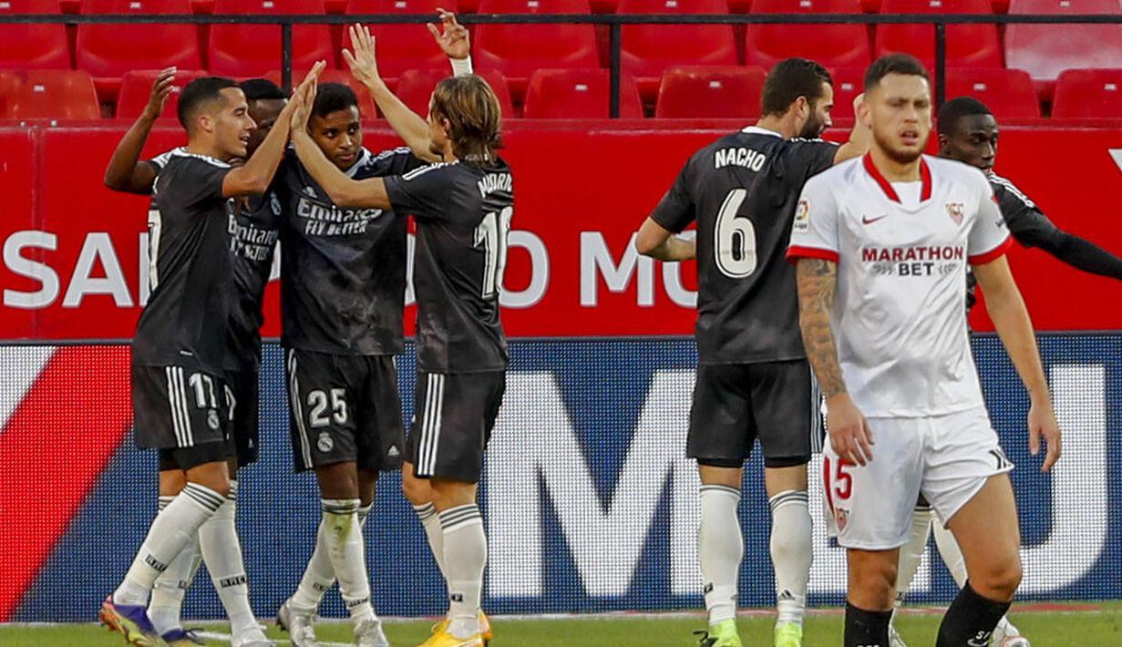 Para pemain Real Madrid merayakan gol yang dicetak ke gawang Sevilla pada laga Liga Spanyol di Stadion Ramon Sanchez Pizjuan, Minggu (6/12/2020). Real Madrid menang dengan skor 1-0. (AP/Angel Fernandez)