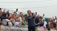 Presiden Joko Widodo berswafoto bersama saat pembentangan Kain Jumputan Palembang terpanjang di atas Jembatan Ampera (Liputan6.com / Nefri Inge)