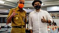 Ketua Umum Kagama, Ganjar Pranowo bersama Vokalis Padi Reborn, Fadly usai acara penyerahan lagu Kagama Bhakti di Semarang, Jawa Tengah, Senin, 22 Februari 2021.