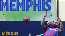 Dalam kesempatan tersebut, Memphis Depay menunjukkan kebolehannya mengolah si kulit bundar dihadapan awak media. (Foto: AFP/Lluis Gene)