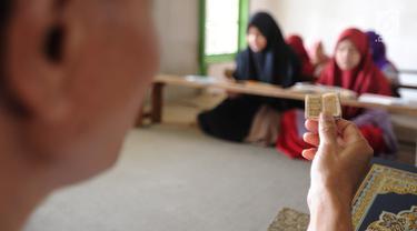 Kyai Tubagus Muhammad Tamyiz mengaji dengan  Al Quran mini bertinta emas saat mengajar  para santri  memaknai Kitab Kuning' di Pondok Pesantren Almiizan, Kabupaten Bogor, Jawa Barat, Zenin, (20/5/2019). Al Quran mini ini berukuran 10 mm x 10 mm. (merdeka.com/Arie Basuki)
