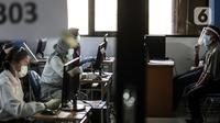Pengawas dan peserta mengenakan masker, pelindung wajah, dan sarung tangan saat mengikuti Seleksi Bersama Masuk Perguruan Tinggi Negeri (SBMPTN) di Universitan Negeri Jakarta, Minggu (5/7/2020). Sebanyak 42.463 peserta mengikuti SBMPTN dengan prosedur protokol kesehatan. (Liputan6.com/Faizal Fanani)
