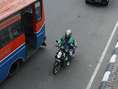 Pengendara sepeda motor mengoperasikan gawainya saat berkendara di Jakarta, Jumat (8/2). Polisi akan melakukan tindakan hukum berupa tilang kepada pengendara yang menggunakan GPS saat berkendara. (Liputan6.com/Immanuel Antonius)