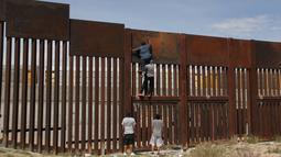 Sejumlah pemuda Meksiko berusaha memanjat tembok besi perbatasan antara Meksiko dan Amerika Serikat di negara bagian Chihuahua, Meksiko (6/4). Mereka menyeberang secara ilegal ke Sunland Park dari Ciudad Juarez. (AFP/Herika Matinez)