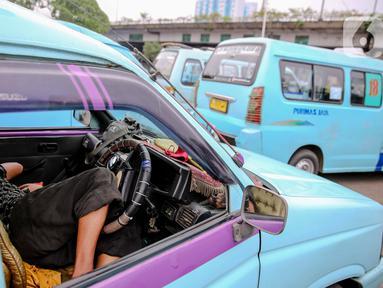 Sopir beristirahat di dalam angkutan kota (angkot) di Terminal Kampung Melayu, Jakarta, Kamis (30/4/2020). Ketua Organda DKI Shafruhan Sinungan mengatakan dari sekitar 85.900 kendaraan yang berada di bawah naungannya, hanya 8.000-8.600 unit yang masih dapat beroperasi. (Liputan6.com/Faizal Fanani)