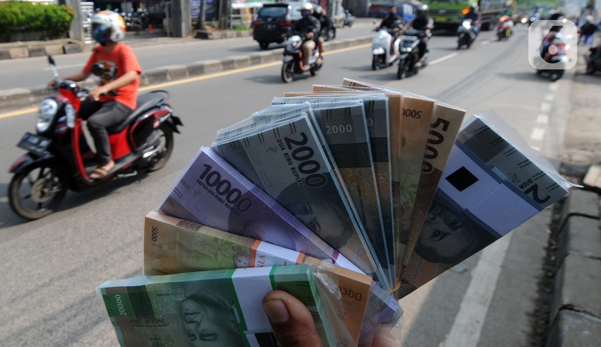 Penjual jasa penukaran uang menawarkan uang baru di kawasan Jalan Raya Parung, Bogor, Jawa Barat, Jumat  (7/5/2021). Penjual jasa yang marak jelang Idul Fitri tersebut banyak dijumpai di sejumlah jalan protokol. (merdeka.com/Arie Basuki)