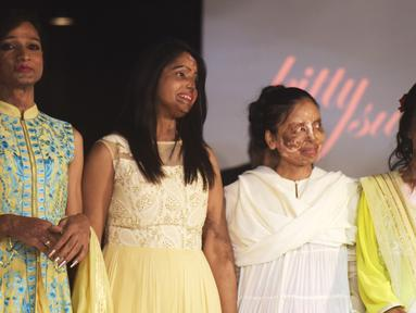 """Sejumlah wanita korban kekerasan dan penyiraman air keras berpose diatas panggung saat peragaan busana di New Delhi, India (25/11). Peragaan busana ini diselenggarakan oleh LSM setempat yang bertema """"Make Love Not Scars"""". (AFP Photo/Dominique Faget)"""