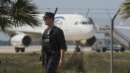 Petugas melakukan penjagaan di dekat pesawat EgyptAir, yang membawa 55 penumpang dan tujuh kru, di Bandara Larnaca, Selasa (29/3). Pesawat yang bertolak dari Alexandria menuju Kairo itu dibajak dan dipaksa mendarat di Siprus. (REUTERS/Yiannis Kourtoglou)