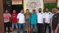 Foto: AT (baju biru), DPO kasus pembunuhan saat diamankan polisi (Liputan6.com/Ola Keda)