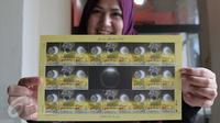 Petugas menunjukan perangko edisi Gerhana Matahari Total di Kantor Pos Indonesia, Jakarta, (25/2). Pos Indonesia (Persero) menerbitkan prangko edisi khusus tersebut dalam rangka menyambut peristiwa gerhana matahari total. (Liputan6.com/Angga Yuniar)