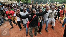 Ratusan mahasiswa Aliansi Mahasiswa Papua (AMP) menari sambil berteriak di lapangan Sahabara Polda Metro, Jakarta, Selasa (1/12/2015). Mereka menunggu ratusan kawan mereka yang diamankan Polisi. (Liputan6.com/Yoppy Renato)