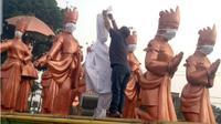 Tajri Danur, seorang diri melakukan aksi pemasangan masker dan kain kafan di patung penari sekapur sirih yang menjadi simbol selamat datang di Kota Jambi, Kamis (19/9/2019). (Liputan6.com/Gresi Plasmanto)