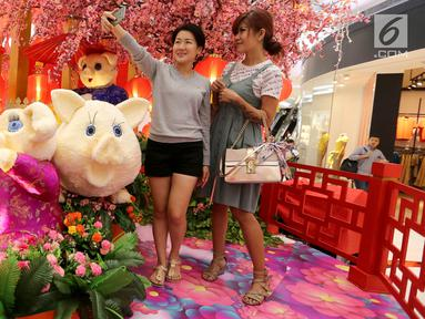 Pengunjung berswafoto bernuansa Imlek di atrium Lippo Mall Puri, Jakarta, Jumat (01/2). Nuansa dekorasi bermacam aneka bunga dan shio Babi menjadi spot foto bagi pengunjung mal. (Liputan6.com/Fery Pradolo)