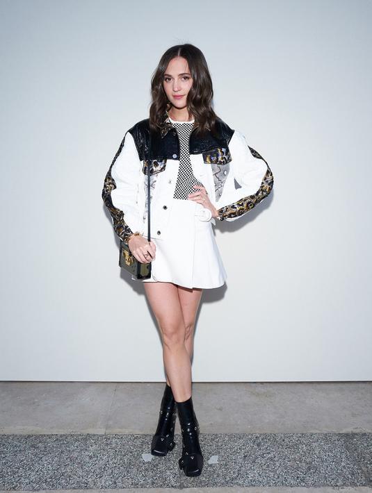 Bintang film Tomb Raider, Alicia Vikander tampil preppy style dengan balutan jacket dan mini skirt warna selaras. Gayanya pun disempurnakan dengan sock boots. (Dok/Louis Vuitton).