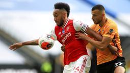 Striker Arsenal, Pierre-Emerick Aubameyang, berebut bola dengan pemain Wolverhampton Wanderers, Romain Saiss, pada laga Premier League di Stadion Molineux, Sabtu (4/6/2020). Arsenal menang dengan skor 2-0. (AP/Michael Steele)