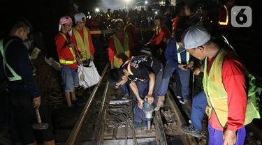 Sejumlah petugas merevitalisasi wesel rel di Stasiun KA Gambir, Jakarta, Kamis (14/2/2020) malam. PT KCI dan PT KAI Daop 1 Jakarta mengganti wesel rel di Stasiun Gambir dan Stasiun Jakarta Kota secara paralel yang akan berlangsung pada 13-23 Februari 2020. (Liputan6.com/Herman Zakharia)
