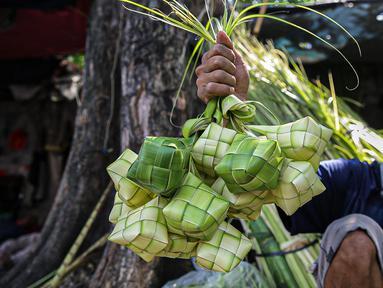 Pedagang menunjukkan cangkang ketupat di kawasan Palmerah, Jakarta, Minggu (18/7/2021). Pemberlakuan PPKM Darurat membuat penjualan cangkang ketupat jelang Idul Adha tahun ini sepi pembeli. (Liputan6.com/Faizal Fanani)