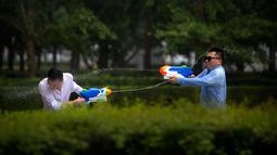 Tiga pekerja kantor bermain semprot-semprotan air di luar kantor, Beijing, (13/7). Karyawan di China terkadang menghabiskan waktu berjam-jam di tempat kerja dan beralih bermain dengan ide kreatif untuk menghilangkan stres. (AP Photo/Mark Schiefelbein)