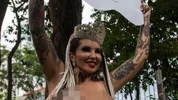 """Penari Samba, Boing Boing dari sekolah Samba Tautape memegang poster yang bertuliskan """"Juara"""" sambil keliling Jalan Paulista di Sao Paulo, Brasil (2/3). (AFP Photo / Nelson Almeida)"""