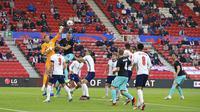 Penjaga gawang Inggris Jordan Pickford meninju bola saat melawan Austria pada pertandingan persahabatan di Stadion Riverside, Middlesbrough, Inggris, Rabu (2/6/2021). Inggris mengalahkan Austria dengan skor 1-0. (Lindsey Parnaby, Pool via AP)