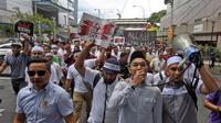 Massa melakukan aksi unjuk rasa menolak pemerintah Malaysia meratifikasi penghapusan diskriminasi rasial (AP via Bernama)