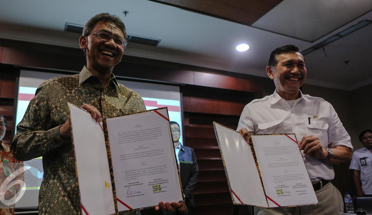 Luhut Binsar Pandjaitan (kanan) dan Ardan Adi Perdana  memperlihatkan MoU di Gedung Bina Graha, Jakarta, Jumat (10/7/2015).  MoU ini akan menjadi landasan pengawasan serta pengendalian 100 program prioritas Presiden Jokowi. (Liputan6.com/Faizal Fanani)
