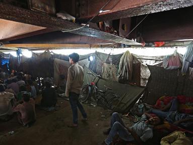Sejumlah orang menonton film di bioskop darurat yang terletak di bawah jembatan di kuartal tua Delhi, India (25/5). Bioskop ini berada di bawah jembatan berusia 140 tahun di ibukota India. (REUTERS/Cathal McNaughton)