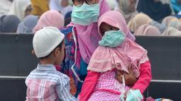 Umat muslim mengenakan masker saat mendengarkan ceramah usai melaksanakan salat Idul Adha di halaman Masjid Raya Annur, Kota Pekanbaru, Riau, Minggu (11/8/2019). Kabut asap imbas kebakaran hutan dan lahan (karhutla) menyelimuti pelaksanaan salat Idul Adha 2019 di Pekanbaru. (Wahyudi/AFP)