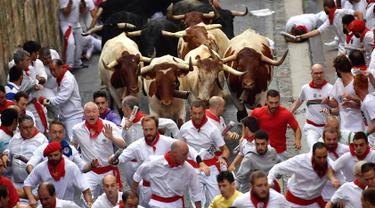 Peserta bersuka ria berlari di samping banteng selama Festival San Fermin di Pamplona, Spanyol, Senin (9/7). Festival berbahaya ini diikuti oleh peserta dari seluruh penjuru dunia. (AP Photo/Alvaro Barrientos)