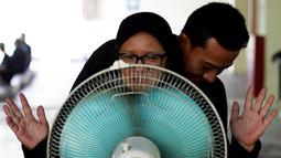Calon pengemudi ojek online berdiri di depan kipas angin saat mengikuti tes bau badan di sebuah tempat parkir bawah tanah di Jakarta, 9 Januari 2016. Uji bau badan ini dilakukan demi meningkatkan kualitas pelayanan. (REUTERS/Garry Lotulung)