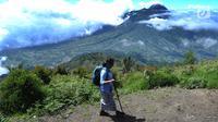 Seorang pendaki melintasi pemandangan Gunung Merapi dari atas Gunung Merbabu di Selo, Boyolali, Jawa Tengah, Sabtu (2/2/2019). Aktivitas Gunung Merapi dalam beberapa hari terakhir masih tinggi dan masih berada di level 2 atau waspada (Merdeka/Arie Basuki)