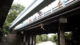Seoarang bocah laki-laki melompat dari jembatan ke sungai saat ia bermain di sungai dengan arus yang sangat deras akibat hujan lebat di bawah jembatan di Manila, Filipina (11/6). (AFP Photo/Noel Celis)
