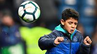 Aksi putra Cristiano Ronaldo, Cristiano Ronaldo Jr saat menunjukkan kebolehannya mengontrol bola usai pertandingan antara Real Madrid dan Real Sociedad di stadion Santiago Bernabeu di Madrid, Spanyol (10/2). (AFP Photo/Gabriel Bouys)