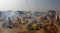 Orang suci Hindu membakar kotoran sapi kering dalam ritual Basant Panchami dalam festival tahunan Magh Mela di Allahabad, India, Senin (22/1). Basant Panchami dilakukan di kawasan Sangam, pertemuan Sungai Gangga dan Yamuna. (AP Photo/Rajesh Kumar Singh)