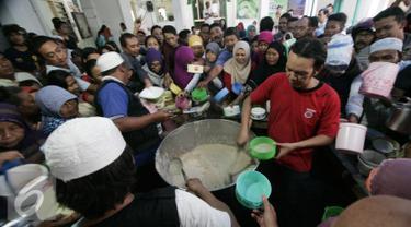 Pengurus masjid membagikan bubur kepada masyarakat di Masjid Darussalam,Solo, Selasa (7/6).Tradisi bubur Ramadan diselenggarakan dengan rata-rata 1100 porsi/hari. (Liputan6.com/Boy Harjanto)
