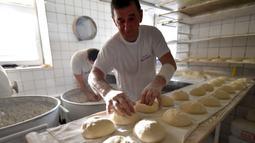 Pekerja membuat adonan somun di sebuah toko roti di kota tua Sarajevo, Bosnia and Herzegovina, Kamis (30/4/2020). Roti somun terbuat dari tepung, air hangat, dan garam sebagai penyedap. (ELVIS BARUKCIC/AFP)