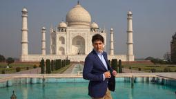 Perdana Meneteri (PM) Kanada Justin Trudeau merapikan jasnya sebelum berpose di depan Taj Mahal di sela-sela kunjungan ke India, Minggu (18/2). PM Kanada mengunjungi Taj Mahal bersama istri dan anak-anaknya. (AP/Manish Swarup)