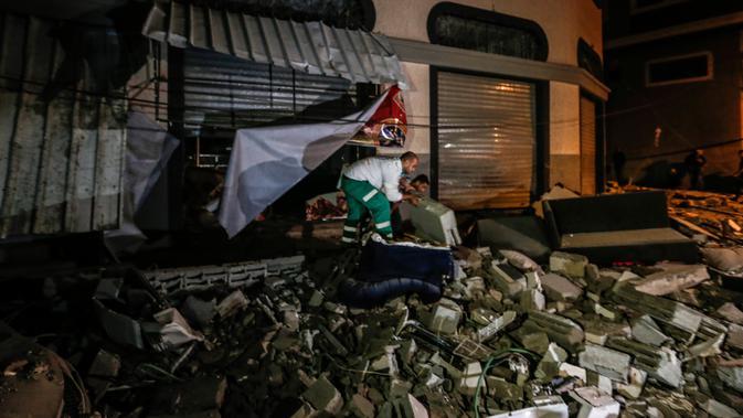 Warga memeriksa rumah komandan Jihad Islam Baha Abu Al-Ata setelah serangan rudal Israel di Kota Gaza, Palestina, Selasa (12/11/2019). Kementerian Kesehatan di Gaza membenarkan bahwa dua orang tewas dalam serangan itu. (MAHMUD HAMS/AFP)