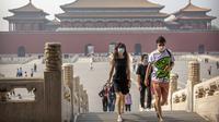 Para pengunjung mengenakan masker saat berjalan di Kota Terlarang, Beijing, China, Jumat (1/5/2020). Kota Terlarang kembali dibuka setelah ditutup lebih dari tiga bulan karena pandemi virus corona COVID-19. (AP Photo/Mark Schiefelbein)