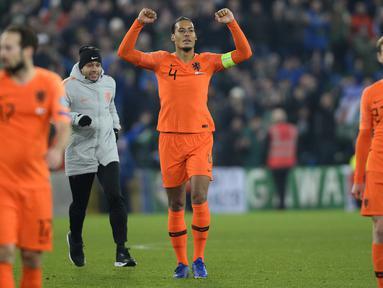 Bek Belanda, Virgil Van Dijk, merayakan keberhasilan lolos ke Piala Eropa 2020 usai melawan Irlandia Utara di Windsor Park, Belfast, Sabtu (16/11). Kedua negara bermain imbang 0-0. (AFP/Mark Marlow)