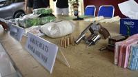 Senjata api dan peluru tajam serta barang bukti kasus narkoba yang disita Polresta Pekanbaru dari dua pemuda. (Liputan6.com/M Syukur)