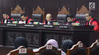 Hakim Mahkamah Konstitusi, Wahiduddin Adams (tengah) membacakan nota putusan perkara pengujian undang-undang tentang ASN, Sistem Pendidikan Nasional, Pendidikan dan Gelar Profesi, di Gedung MK, Jakarta, Kamis (14/2). (Liputan6.com/Helmi Fithriansyah)