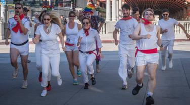 """Peserta berdandan seperti badut mengajar pejalan kaki selama acara parodi tahunan """"Running of the Clowns"""" i Pasadena, California pada 20 Oktober 2019. Lari dikejar kawanan badut ini merupakan parodi yang mengolok-olok lomba dikejar banteng di Spanyol. (Mark RALSTON / AFP)"""