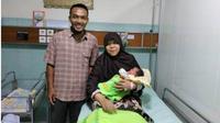 Ibu bayi kembar tiga Esti Muryani menggendong salah satu bayinya didamping suami, Trianto, di Ruang Anisa RS PKU Muhammadiyah Solo, Senin (19/11 - 2018). (Solopos/Ratih Kartika)