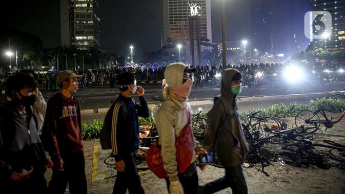 Sejumlah orang berjalan usai demonstrasi yang berujung anarkis di kawasan Bundaran HI, Jakarta, Kamis (8/10/2020). Massa membakar sejumlah barang saat demonstrasi menolak pengesahan UU Cipta Kerja. (Liputan6.com/Faizal Fanani)