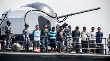 Sembilan Tersangka perompak dihadirkan oleh Anggota TNI AL di Surabaya, Jawa Timur, (10/5). Sembilan tersangka diduga melakukan pembajakan terhadap kapal tanker berbendera Singapura di perairan Tanjung Puting, Kalimantan. (AFP PHOTO/JUNI KRISWANTO)