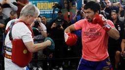 Petinju Manny Pacquiao (kanan) berlatih dengan pelatih Freddie Roach di sebuah klub tinju di Los Angeles, AS, Rabu (9/1). Pacquiao akan melawan Adrien Broner pada 19 Januari mendatang. (AP Photo/Damian Dovarganes)