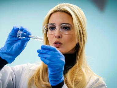 Ivanka Trump menggunakan pipet mengukur tingkat nikotin dalam rokok ketika melakukan kunjungan di laboratorium di  Waukee Innovation and Learning Centre di Waukee, Iowa, (19/3). (Rodney White/The Des Moines Register via AP)