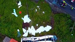 Kondisi sebuah bus pariwisata berisi rombongan turis dari Jerman yang terguling di Kota Canico, Pulau Madeira, Portugal, Rabu (17/4). Kecelakaan terjadi di mana bus yang mengangkut 55 otang turis terguling saat membelok dari jalan sempit yang curam. (STRINGER / AFP)
