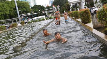 Anak-anak berenang di kolam air mancur penghias kawasan Pasar Baru, Jakarta, Selasa (29/1). Keterbatasan lahan bermain menyebabkan sebagian anak di Ibukota bermain tidak pada tempatnya, meskipun berbahaya bagi keselematan. (Liputan6.com/Immanuel Antonius)